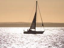 En yacht på solnedgången i Solenten Arkivfoto