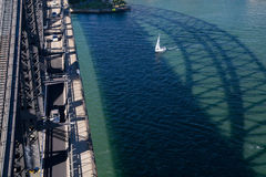 En yacht seglar under Sydney Harbour Bridge Royaltyfria Bilder
