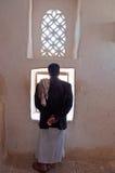 En yemeni man som ut ser fönstret inom Dar al-Hajar, Dar al Hajar, vaggaslotten, kunglig slott, Yemen Arkivfoto