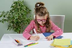 En yngre schoolgirll i exponeringsglas som skriver något i förskriftsbok a Royaltyfria Foton