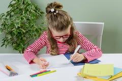 En yngre skolflicka med exponeringsglas skriver något med henne lämnade Royaltyfri Fotografi