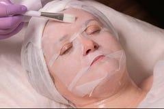En yrkesmässig cosmetologist i lila handskar borstar uppföda stelnar till och med en maskering på patienten med en borste Kosmeti arkivfoto