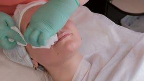 En yrkesmässig cosmetologist-terapeut torkar kvarlevorna av en genomskinlig skönhetsmedel stelnar från en kvinnlig framsida Flick stock video