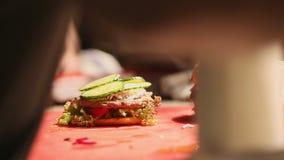 En yrkesmässig kock förbereder en ostburgare med en stor kotlett och en sallad stock video