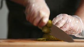 En yrkesmässig kock klipper en gurka i handskar arkivfilmer