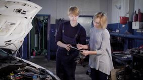 En yrkesmässig mekaniker tar häftet från besökaren av denomsorg mitten för att reparera bilen i service lager videofilmer