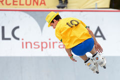 En yrkesmässig skateboradåkare på Inline åka skridskor hoppar konkurrens Arkivfoto