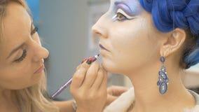 En yrkesmässig sminkkonstnär förbereder en modell för en fotofors arkivfilmer