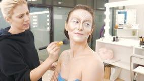 En yrkesmässig sminkkonstnär gör sminket av modellen Applicera en special borste med en tonal målarfärg Förberedelse för lager videofilmer