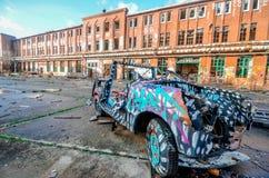 En yttersida av en utan tak antik tappning, den roadster mönstrade bilen parkerade framme av en byggnad för gammal skola i Berlin arkivbilder