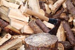 En yxa på ett trä, trädjournal En yxa klibbade i en inloggningsframdel av en hög av trä, ordnar till för att hugga av och övervin Arkivfoton