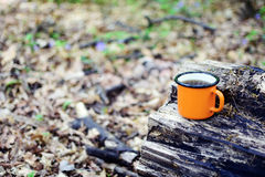 Enamel cup of tea. Cup with hot tea stands on a log Stock Image