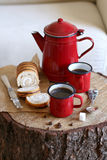 Enamel mugs with hot coffee and enamel kettle on a rustic wooden board Royalty Free Stock Photo