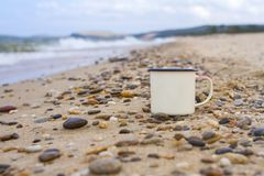 Enameled camp mug on the pebbles of the sandy shore of Lake Baikal during a wave on a mountain background in the summer. Enameled camp mug on the pebbles of the Royalty Free Stock Image