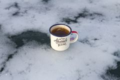 Enameled camping mug of the traveler with hot lavender tea and tea bag on the beautiful scenic ice in the form of a cloud. Enameled camping mug of the traveler Stock Photography