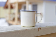 Enameled camping mug on a wooden texture veranda in winter on a wooden houses background in the suburbs. Stock Image