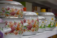Enameled cooking pots in the supermarket on the shelf stand in a row. Close up Stock Photography