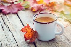 Cup of coffee and fallen maple leaves on wooden boar royalty free stock photography