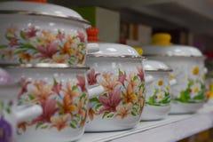 Enameled faisant cuire des pots dans le supermarché sur le support d'étagère dans une rangée Photographie stock