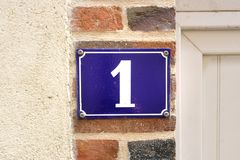 Enameled house Number 1. Enameled house number one 1 ataached to a stone wall Royalty Free Stock Photos