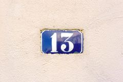 Number 13. Enameled house number thirteen 13 embedded in a plastered wall Royalty Free Stock Photos