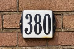 House number three hundred and eighty 380. Enameled house number three hundred and eighty 380 Royalty Free Stock Photos