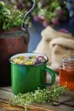 Enameled mug of healing herbs, old tea kettle, honey jar and medical plants. Royalty Free Stock Image