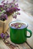Enameled mug of thyme healing herbs. Enameled mug of thyme healing herbs and wooden box full of thymus serpyllum for healthy herbal tea. Herbal medicine Stock Photo