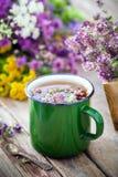 Enameled mug of thyme and medicinal herbs bunch on background. Enameled mug of thyme healing herbs and medicinal herbs bunch on background. Herbal medicine Royalty Free Stock Photography
