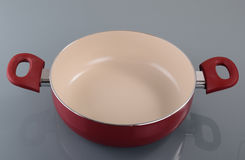 Enameled red pan. Enameled pan with handle on gray background Royalty Free Stock Photo