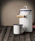 Enameled tin mug and kitchen storage canister. Enameled white tin mug and kitchen storage canister with a lid and handle standing on an old grunge wooden counter Royalty Free Stock Image