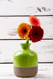 Enameled vase with gerberas. Flowers in vase on wood. How to grow plants. Beautiful items of room design Royalty Free Stock Photos
