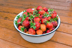 Enamelled bowl with strawberries standing on the table Royalty Free Stock Photo