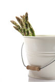 Enamelled bucket with some fresh green Asparagus. Isolated on white Royalty Free Stock Image