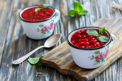 Enamelled mug with cranberry jelly and a teaspoon. Royalty Free Stock Image