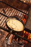 Enamelled pan on fire. Preparation of mushroom steak sauce. Fire in the camp. Enamelled pan on fire. Preparation of mushroom steak sauce. Fire in the camp Stock Image