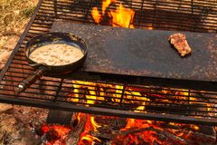 Enamelled pan on fire. Preparation of mushroom steak sauce. Fire in the camp. Enamelled pan on fire. Preparation of mushroom steak sauce. Fire in the camp Stock Photos