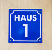 Enamelled plate with house number one. White lettering on a blue background Stock Image
