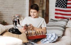 Enamorado con jugar al muchacho que mira su juguete Imágenes de archivo libres de regalías