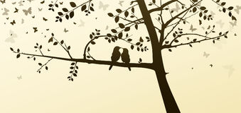 Enamored Birds Sitting on a Tree in a Romantic Setting. On a light background Royalty Free Stock Photo