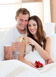 Enamored couple drinking champagne lying in bed. Enamored couple drinking champagne with strawberries lying in bed at home stock photos