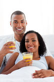 Enamored couple drinking lying on their bed Royalty Free Stock Photography