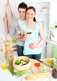 Enamored couple drinking wine in the kitchen Royalty Free Stock Images