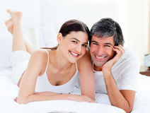 Enamored couple embracing lying on their bed. Portrait of an enamored couple embracing lying on their bed royalty free stock photos