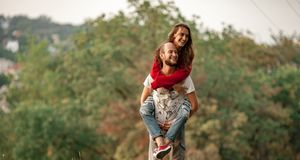 Young man lifted up girl on his back and carries her. Stock Photos