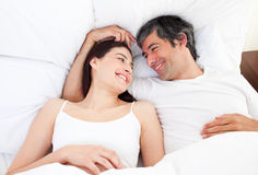Enamored couple hugging lying in their bed. At home royalty free stock photography