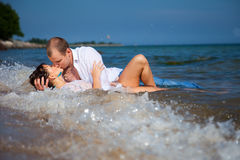 Enamored couple kissing in waves of sandy beach Stock Images