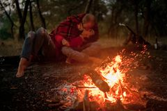 Enamored couple lies, hugs and kisses in forest against background of bonfire flame and sparks. Enamored couple lies on ground, hugs and kisses on picnic in stock photo