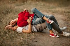 Enamored couple lies, smiles and embraces on forest path. Girl is lying on guy stock photos