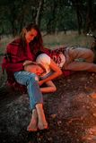 Enamored couple on picnic in forest. Young men is lying on girl`s lap. Visible glow from campfire. Closeup royalty free stock photo